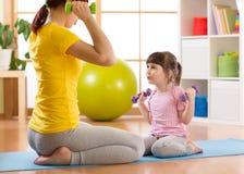 Mujer y su hija del niño que hacen ejercicios de la aptitud con pesas de gimnasia Foto de archivo