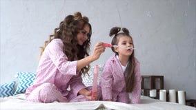 Mujer y su hija que están llevando burbujas de jabón del soplo de los pijamas en el dormitorio almacen de video