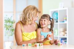 Mujer y su hija que juegan con los cubos Imagen de archivo libre de regalías