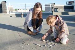 Mujer y su hijo que se sientan en el tejado Imágenes de archivo libres de regalías
