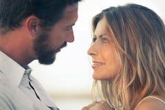 Mujer y su hombre cara a cara en una puesta del sol Imagen de archivo libre de regalías
