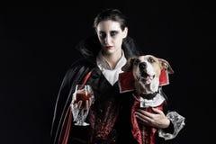Mujer y su perro en los trajes similares del vampiro para Halloween usted foto de archivo