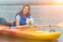 Mujer y su perro en un kajak Fotografía de archivo