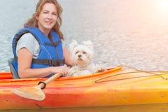 Mujer y su perro en un kajak Foto de archivo libre de regalías
