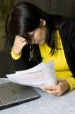 Mujer y sus cuentas mensuales imagen de archivo