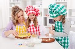 Mujer y sus hijas en la cocina Imágenes de archivo libres de regalías