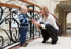 Mujer y sus pequeñas cámaras digitales del uso del hijo fotos de archivo
