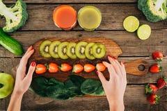 Mujer y tabla de cortar con las verduras frescas y las frutas imágenes de archivo libres de regalías