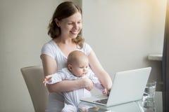 Mujer y un bebé cerca del ordenador portátil imagen de archivo