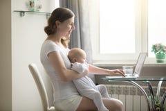 Mujer y un bebé en el ordenador portátil fotos de archivo