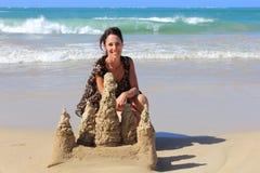 Mujer y un castillo de la arena Imagenes de archivo