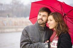 Mujer y un hombre barbudo debajo de un paraguas rojo Fotografía de archivo libre de regalías