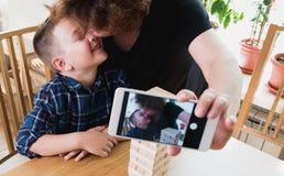 Mujer y un muchacho que hace el selfie en smartphone móvil mientras que juega un bloque que quita el juego que intenta mantener e fotografía de archivo