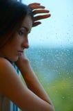 Mujer y ventana lluviosa Imagenes de archivo