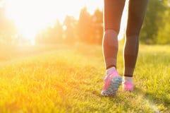 Mujer y zapatillas deportivas, ejercitando en naturaleza Imagen de archivo