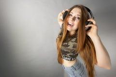 Mujeres adolescentes que llevan los auriculares Imagenes de archivo