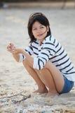 Mujeres adolescentes que se sientan en el shell de la playa y del mar en h Imágenes de archivo libres de regalías