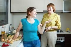 Mujeres adultas junto que cocinan en hogar Imágenes de archivo libres de regalías
