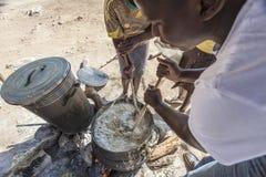 Mujeres africanas que cocinan las gachas de avena sobre el fuego Imágenes de archivo libres de regalías