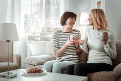 Mujeres alegres de emisión que tienen conversación expresiva durante el desayuno foto de archivo libre de regalías