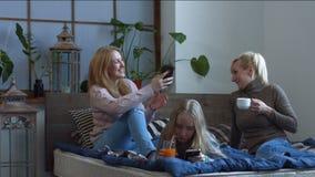 Mujeres alegres que charlan y que cotillean en casa metrajes