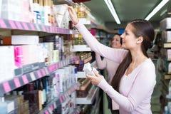 Mujeres alegres que escogen la crema del estante Imagen de archivo