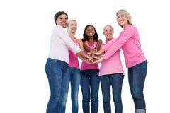 Mujeres alegres que llevan cintas del cáncer de pecho con las manos juntas Imagen de archivo libre de regalías