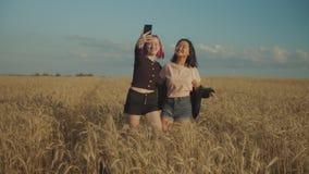 Mujeres alegres que toman el selfie al aire libre en la puesta del sol almacen de metraje de vídeo
