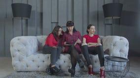 Mujeres alegres que ven las fotos del bebé que descansan sobre el sofá almacen de metraje de vídeo