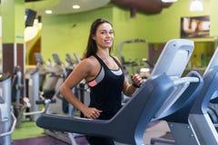 Mujeres aptas que hacen los ejercicios cardiios, corriendo en las ruedas de ardilla en el gimnasio Imagen de archivo