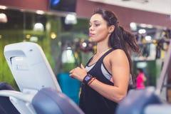 Mujeres aptas que hacen los ejercicios cardiios, corriendo en las ruedas de ardilla en el gimnasio Foto de archivo libre de regalías
