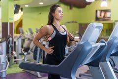 Mujeres aptas que hacen los ejercicios cardiios, corriendo en las ruedas de ardilla en el gimnasio Fotografía de archivo