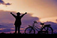 Mujeres asiáticas felices del inconformista de la silueta con la bicicleta Imágenes de archivo libres de regalías