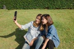 Mujeres asiáticas hermosas atractivas de los amigos que usan un smartphone Adolescente asiático joven feliz en la ciudad urbana m Imagen de archivo