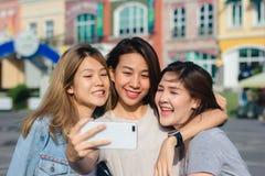 Mujeres asiáticas hermosas atractivas de los amigos que usan un smartphone Adolescente asiático joven feliz en la ciudad urbana m Foto de archivo