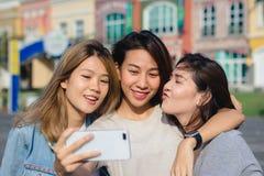 Mujeres asiáticas hermosas atractivas de los amigos que usan un smartphone Adolescente asiático joven feliz en la ciudad urbana m Fotografía de archivo libre de regalías