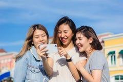 Mujeres asiáticas hermosas atractivas de los amigos que usan un smartphone Adolescente asiático joven feliz en la ciudad urbana m Imágenes de archivo libres de regalías