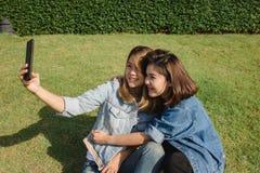 Mujeres asiáticas hermosas atractivas de los amigos que usan un smartphone Adolescente asiático joven feliz en la ciudad urbana m Fotos de archivo