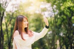 Mujeres asiáticas hermosas jovenes con el pelo marrón largo que toma un selfie en su teléfono en el parque Imagenes de archivo