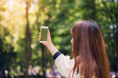 Mujeres asiáticas hermosas jovenes con el pelo marrón largo que toma un selfie en su teléfono en el parque Iluminación natural Imágenes de archivo libres de regalías