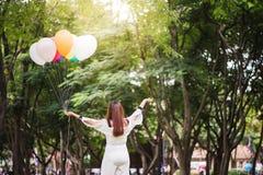 Mujeres asiáticas hermosas jovenes sonrientes con el pelo marrón largo en el parque Foto de archivo