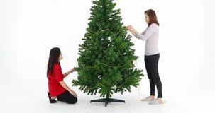 Mujeres asiáticas hermosas que adornan el árbol de navidad metrajes