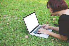 Mujeres asiáticas jovenes del inconformista feliz que trabajan en el ordenador portátil en parque Conceptos de la forma de vida y foto de archivo