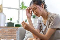 Mujeres asiáticas jovenes en el sufrimiento del sofá del dolor de cabeza y tener cierta fiebre fotos de archivo