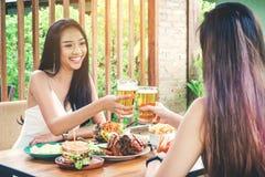 Mujeres asiáticas jovenes que beben los vidrios de la cerveza y del tintineo felices mientras que en imagenes de archivo