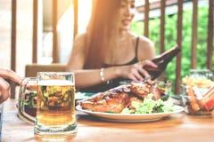 Mujeres asiáticas jovenes que beben los vidrios de la cerveza y del tintineo felices mientras que en imágenes de archivo libres de regalías