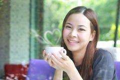 Mujeres asiáticas jovenes que sostienen una taza de café al lado del espejo Imagen de archivo libre de regalías