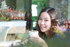 Mujeres asiáticas jovenes que sostienen una taza de café con tono de la fractura por otra parte Fotografía de archivo libre de regalías