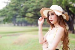 Mujeres asiáticas que llevan el sombrero que se coloca en el parque. Imágenes de archivo libres de regalías