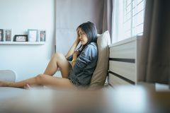 Mujeres asiáticas que se sientan en dormitorio en casa, dolor de cabeza de sensación femenino y problema confuso en vida personal imagenes de archivo
